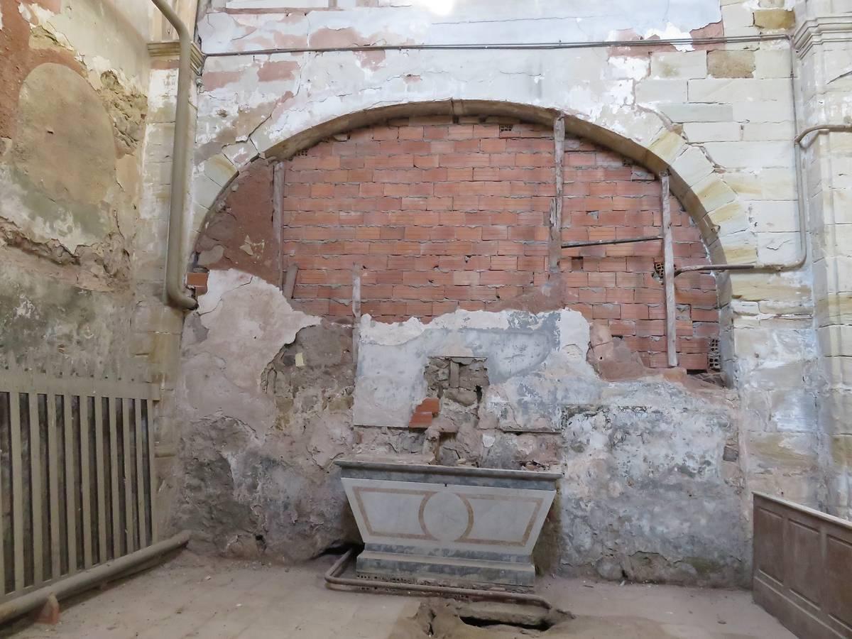 Arc appareillé en pierres de taille, fermé par une cloison en brique contre laquelle repose un autel secondaire