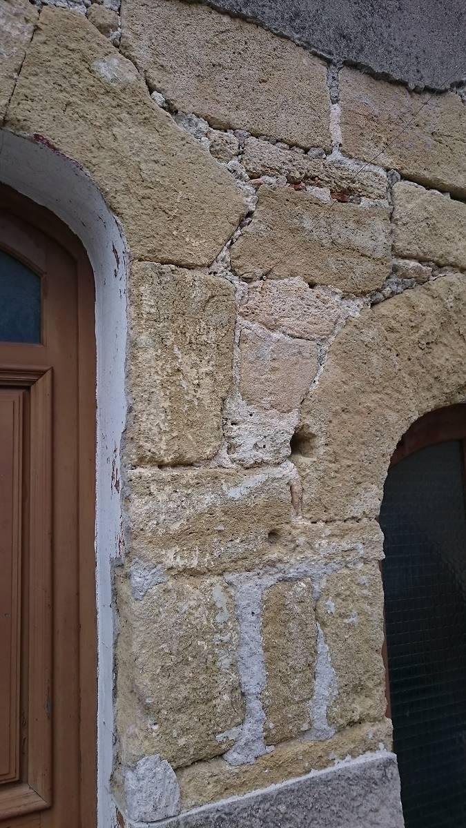 Détail de la façade avec des morceaux de terre cuite dans les joints.