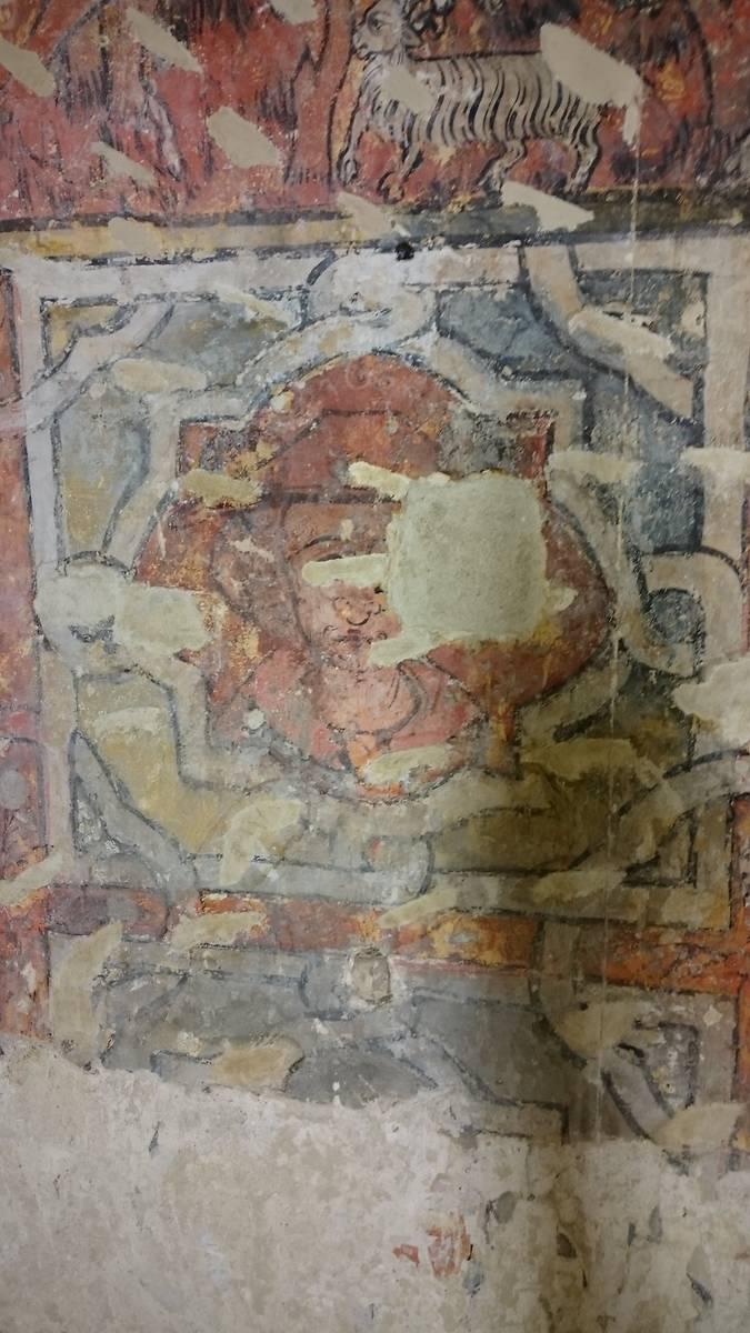 Détail de la frise de polylobes. Ici dans un polylobe à fond rouge se dessine une tête de figure féminine.